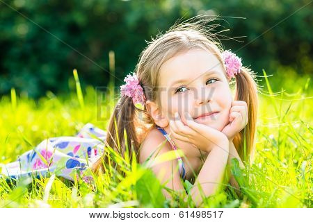 Cute Smiling Little Girl With Two Blond Ponytails Laying On Grass In Summer Park, Outdoor Portrait