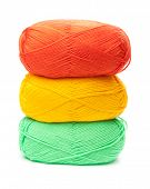stack of yarn skeins in yellow, orange, green colors on white background