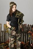 A beautiful young teen by a rustic old fence.  She's wearing camo pants, hat, and gloves and carries