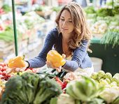 stock photo of stall  - Young woman baying vegetable on the market - JPG