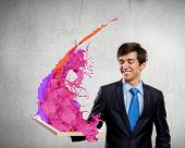 Handsome businessman holding frame with colorful splashes