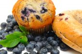 stock photo of bagel  - Fresh blueberries surround a single blueberry muffin and a bagel on a light background - JPG
