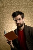Portrait of young man with beard reading book over retro background