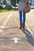 Close-up of woman legs walking on bike alley and arrow sign