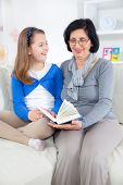 Grandmother and little girl reading a book happy together at home