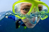 foto of extreme close-up  - Extreme close up underwater portrait of a woman with mask snorkeling in a sea - JPG