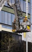 picture of cherry-picker  - color photo of two firemen being lifted in cherry picker for rescue operation - JPG
