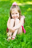 foto of bow-legged  - Cute little girl with long blond hair sitting on grass in summer park putting her hands around her legs outdoor portrait - JPG