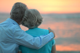 pic of retirement age  - Elderly couple in love at sunset on a summer evening watching sea - JPG