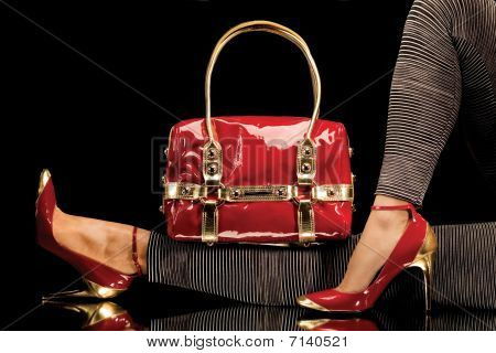 Long legs on high heels and red purse over black