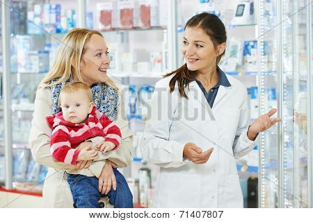 Cheerful female pharmacist chemist consulting woman with little child girl in pharmacy drugstore