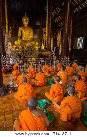 CHIANG MAI, THAILAND - NOVEMBER 22, 2013: Young buddhist monks praying in front of the Buddha image in the temple in Chiang Mai, Thailand on 22 November, 2013