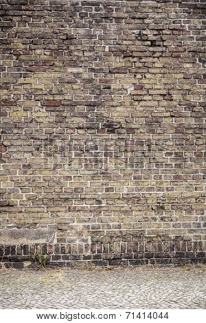 Old Brown Brick Wall With Pavement