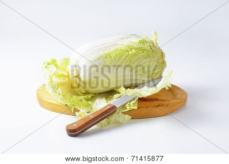 chinese cabbage and kitchen knife on wooden cutting board