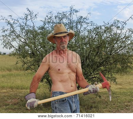 A Shirtless Cowboy Uses A Red Pickax
