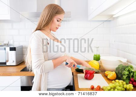 Pregnant woman at kitchen preparing salad