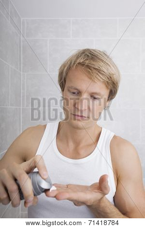 Man removing aftershave moisturizer in bathroom