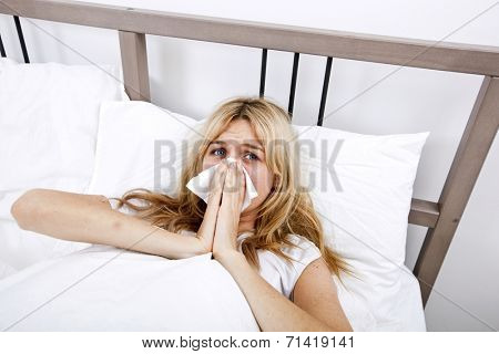 Portrait of woman suffering from cold in bed
