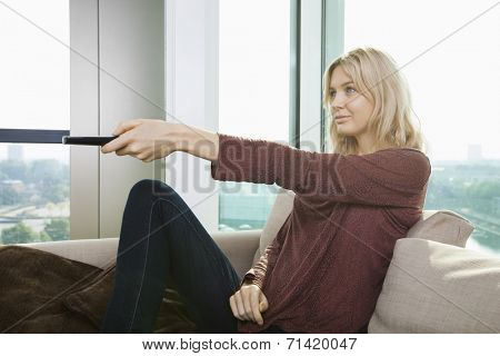 Side view of young woman watching television on sofa at home