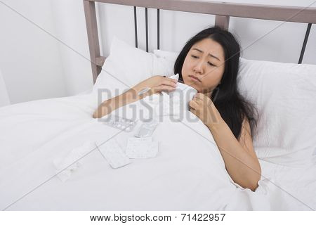 Woman suffering from cold having coffee in bed
