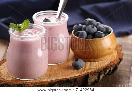 Yogurt With Blueberries In A Glass Jar And Blueberries In A Wooden Bowl