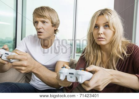Young couple playing video game in living room at home
