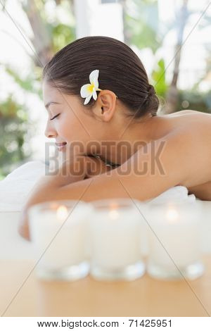 Beautiful brunette relaxing on massage table with salt scrub on back at the health spa