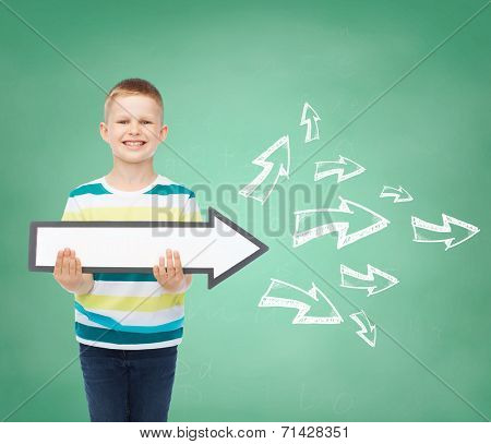 advertising, direction, education and childhood concept - smiling little boy with white blank arrow pointing right over green board with doodles background