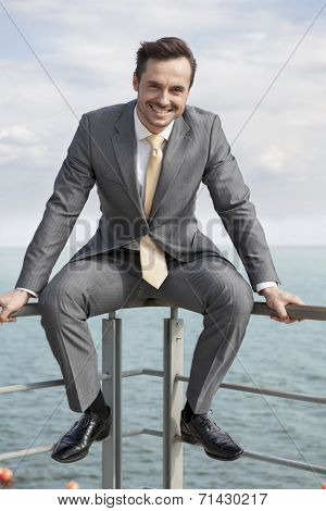 Full-length portrait of happy businessman sitting on terrace railings