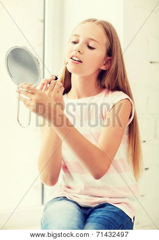 adolescence, beauty, makeup, happy people concept - teenage girl with lip gloss and mirror
