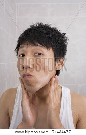 Portrait of mid adult man applying aftershave lotion in bathroom