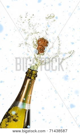 Snow falling against bottle of champagne popping
