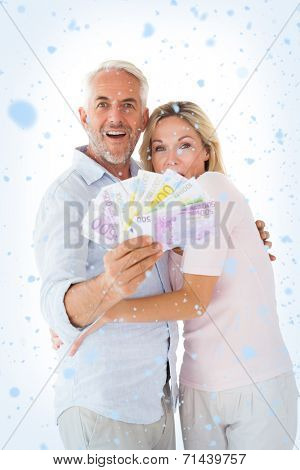 Happy couple flashing their cash against snow falling