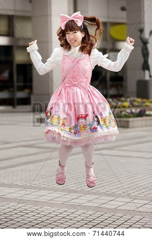 Happy japanese sweet lolita cosplay jumping on a Tokyo sidewalk