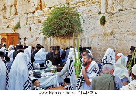 JERUSALEM, ISRAEL - SEPTEMBER 20, 2013: Western Wall of the Temple in Jerusalem. Many religious Jews in traditional white robes gather for prayer. Morning Sukkot.