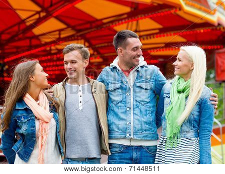 leisure, amusement park and friendship concept - group of smiling friends with carousel on the back