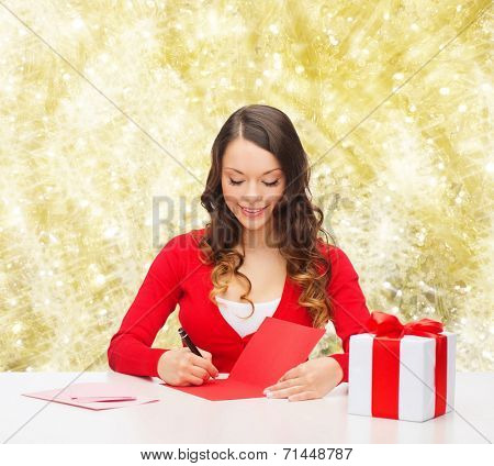 christmas, holidays, celebration, greeting and people concept - smiling woman with gift box writing letter or sending post card over yellow lights background