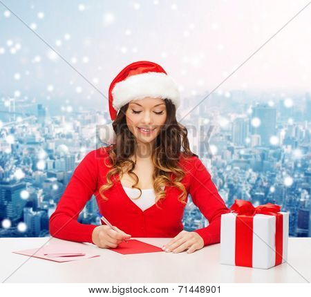 christmas, holidays, celebration, greeting and people concept - smiling woman in santa helper hat with gift box writing letter or sending post card over snowy city background