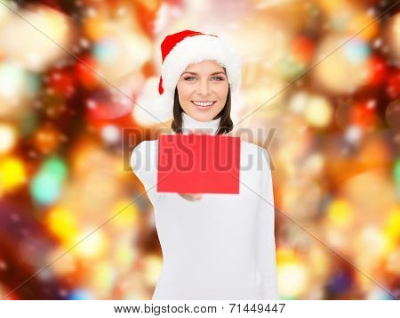 christmas, holdays, people, advertisement and sale concept - happy woman in santa helper hat with blank red card over red lights background