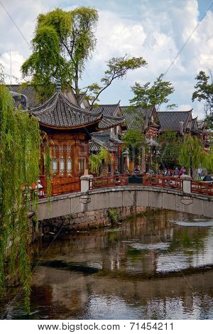 Wooden Houes In Chinese Style, Picturesque Bridge Across The River And Green Willow Trees
