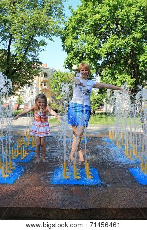 Mother And Daughter Playing In Fountains