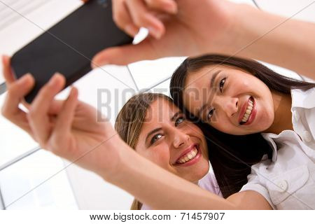 Two Smiling Young Women Taking Self Portrait