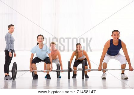 Multiethnic Group With Weightlifting Bar Workout In Fitness Centre