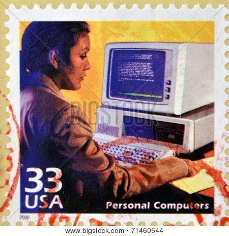 a stamp printed in USA showing an image of a woman using an old computer