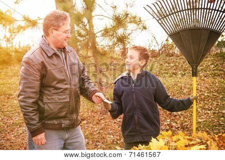 Boy earning money from raking leaves