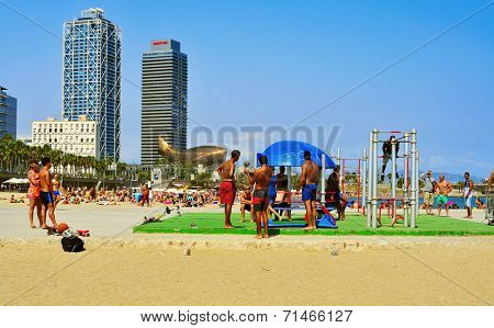 BARCELONA, SPAIN - AUGUST 19: People in an outdoor gym in Barceloneta Beach on August 19, 2014 in Barcelona, Spain. This popular beach hosts 500,000 visitors from everywhere during the summer season