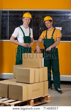 Men With Fork Pallet Truck Full Of Boxes