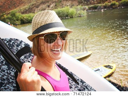 a pretty woman carrying a surf board or stand up paddle board down to the river on a hot summer day