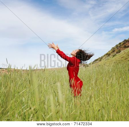 a girl walking in a field letting go