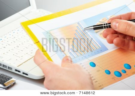 Gráficos de negocios y de la mano masculina con pluma